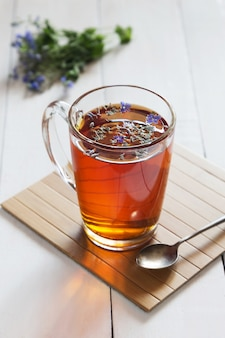 Herbal tea with blossoms in a glass