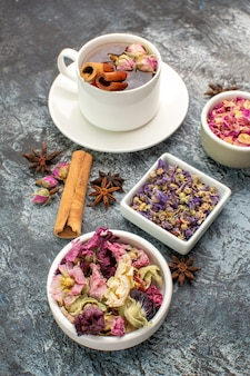 Herbal tea with bowls of dry flower on grey ground