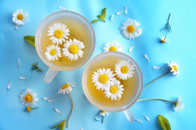 青い表面のガラスのコップにカモミールの花とハーブティー