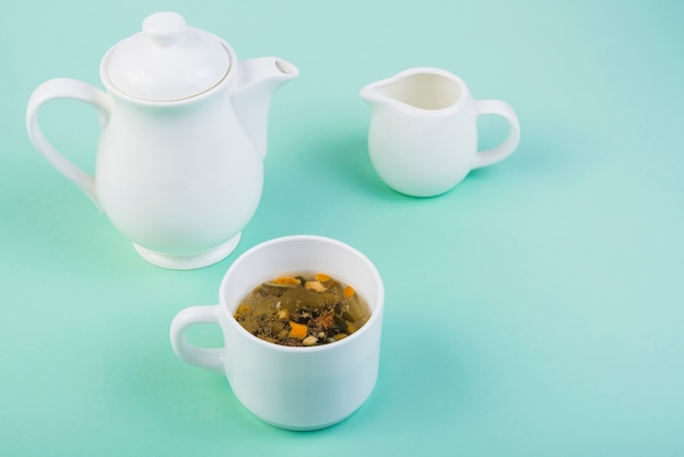 Herbal tea with crockery on turquoise background