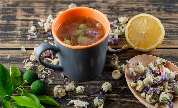 Herbal tea with dried flowers, lemon, limes in a cup on wooden surface