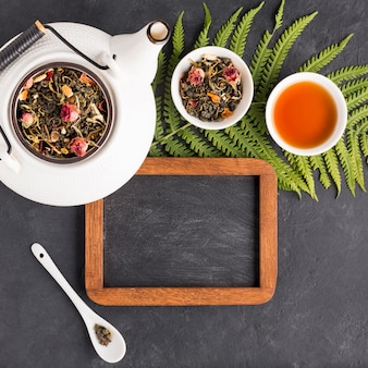 Herbal tea with dried herb and empty slate on black background