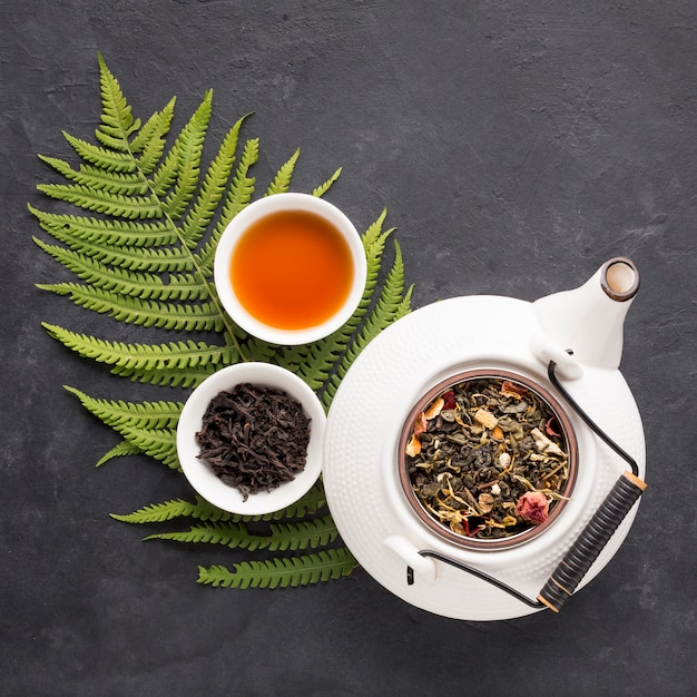 Herbal tea with dried herb and fresh fern leaves on black slate backdrop