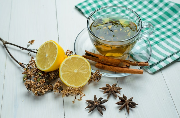 Herbal tea with dried herbs, spice, cinnamon sticks, lemon in a cup on wooden and tea towel high angle view.