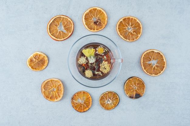 Tè alle erbe con arancia secca su sfondo grigio. foto di alta qualità
