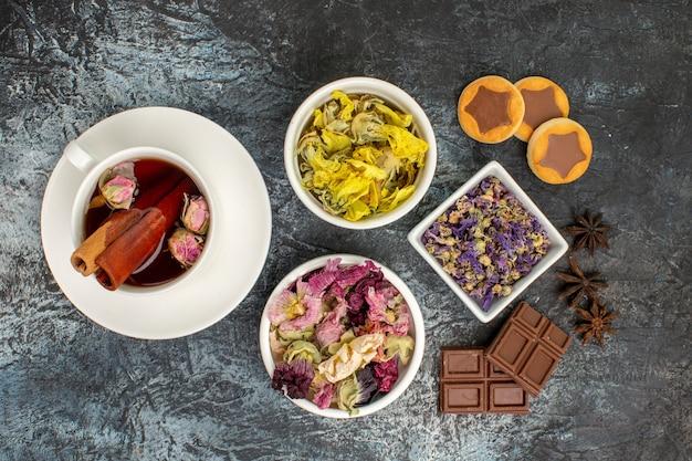 Tisana con fiori secchi e biscotti e barrette di cioccolato e anice su fondo grigio