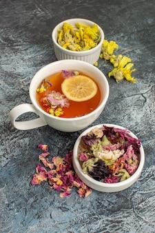 Tisana con fiori secchi e un piatto su fondo grigio