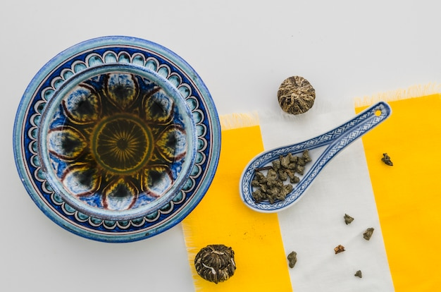 Herbal tea with floral blooming tea ball and oolong tea dust against white background