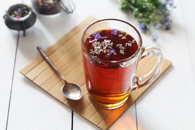 Herbal tea with flowers in transparent glass