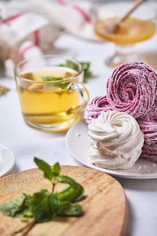 ハチミツとミントのハーブティーと自家製ベリーゼファー。リネンのテーブルクロスで美味しくてヘルシーな朝食。いちごカラントのマシュマロ。