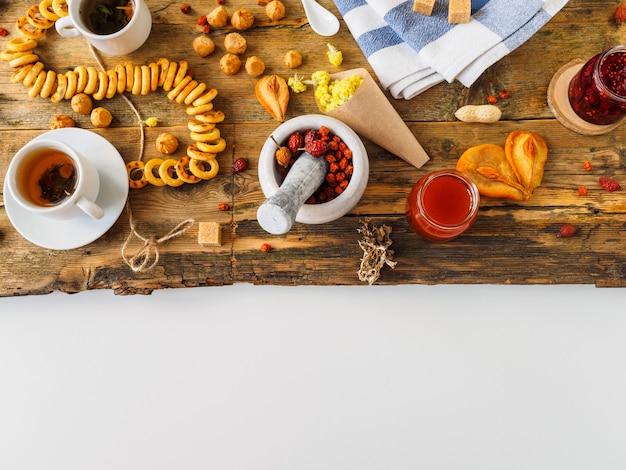 Травяной чай с ингредиентами и сладостями на старой доске.
