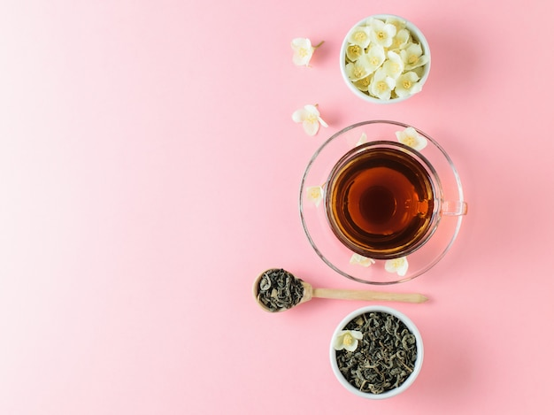 Herbal tea with jasmine and a bowl of flowers on a pink table. the composition of the morning breakfast. flat lay.