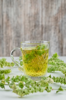 Herbal tea with leaves in a glass cup on white and grungy,