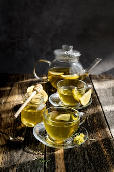 Herbal tea with lemon and honey in glass cup and teapot