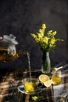 Herbal tea with lemon and honey in glass cup