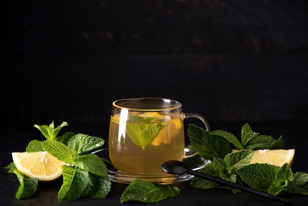 黒のbsckgroundのガラスのマグカップにミントとレモンのハーブティー