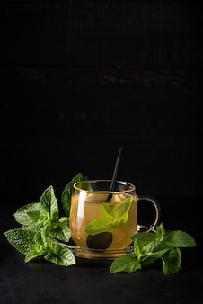 Herbal tea with mint and lemon in a glass mug on black bsckground