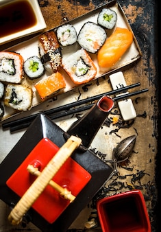 Herbal tea with rolls and sushi on rustic background