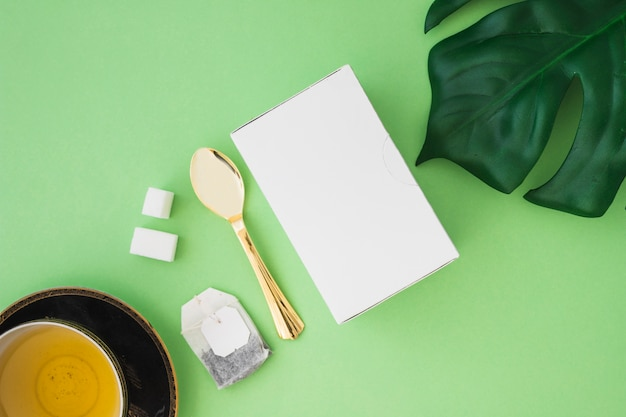 Herbal tea with sugar cubes, tea bag, spoon and box on green background