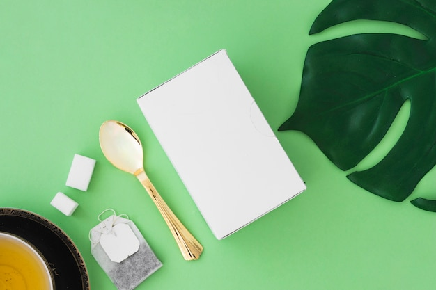 Herbal tea with sugar cubes, tea bag, spoon, leaf and box on green background