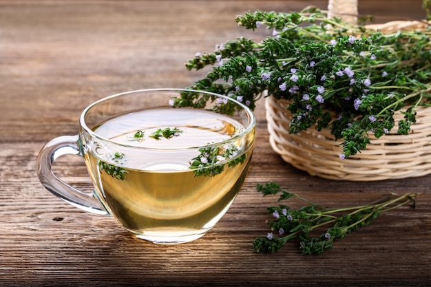 Herbal tea with thyme over rustic wooden background.