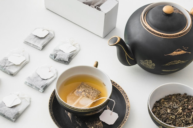 Herbal teabag in the cup on white background