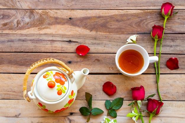 木製の背景にバラのハーブティーカップとティーポット