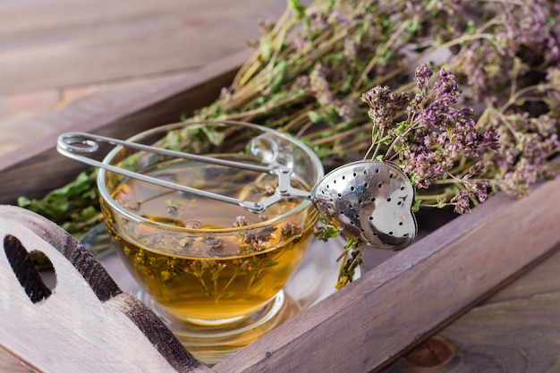 ハーブ療法。テーブルの上の木製トレイにオレガノとハーブの束とお茶