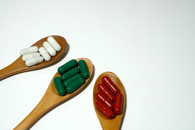 Herbal vitamins in capsule on wooden spoon and white background