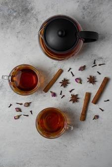 Tè invernale alle erbe nelle tazze e nel bollitore.