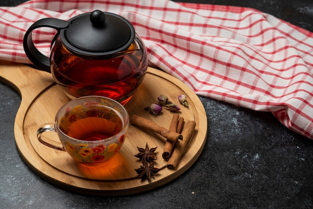 Herbal winter tea in the cups with spices on a wooden board.