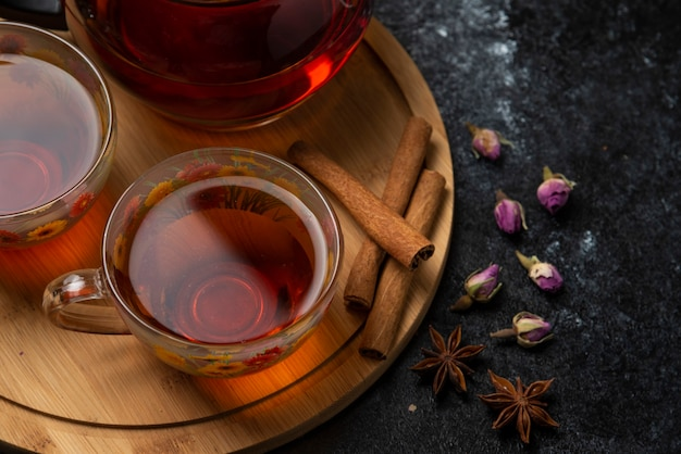 Herbal winter tea in the cups with spices on a wooden platter, top view.