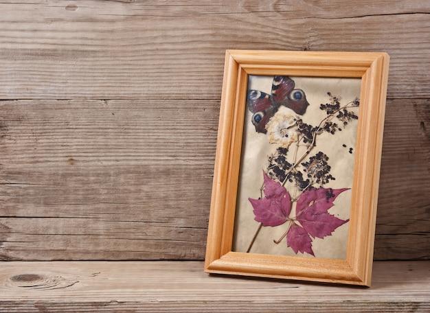 Гербарий в рамке на деревянном фоне