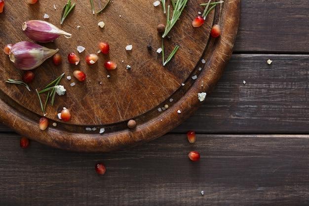 Травы и ингредиенты для приготовления пищи крупным планом на деревенском дереве, вид сверху
