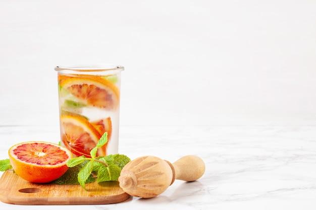 허브와 과일은 피 묻은 오렌지로 물을 주입했습니다. 여름 상쾌한 음료. 건강 관리, 피트니스, 건강한 영양 다이어트 개념.
