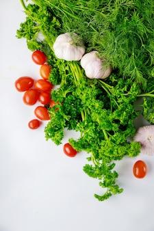 白い背景の上のトマトとハーブとニンニク。健康食。