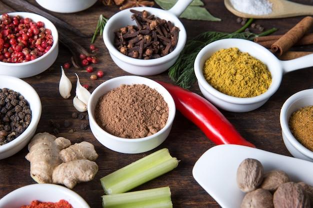 Травы и специи в керамических мисках. ароматические ингредиенты и натуральные пищевые добавки.