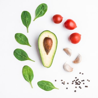 Herbs and vegetables around avocado