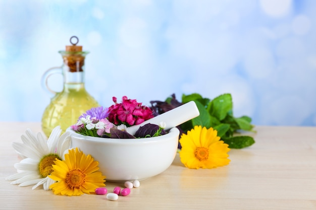 Травы, ягоды, цветы и таблетки на цветном деревянном столе, на ярком