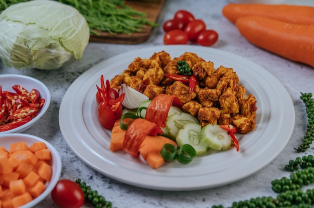 Herbs fried chicken with chili, tomato, cucumber, carrot, and fresh pepper.