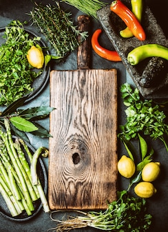 Herbs and spices around wooden cutting board