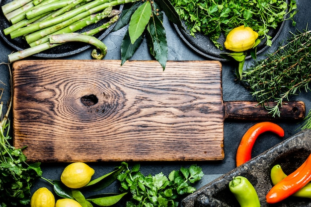 Herbs and spices around wooden cutting board.