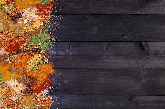 Herbs and spices over black wooden background