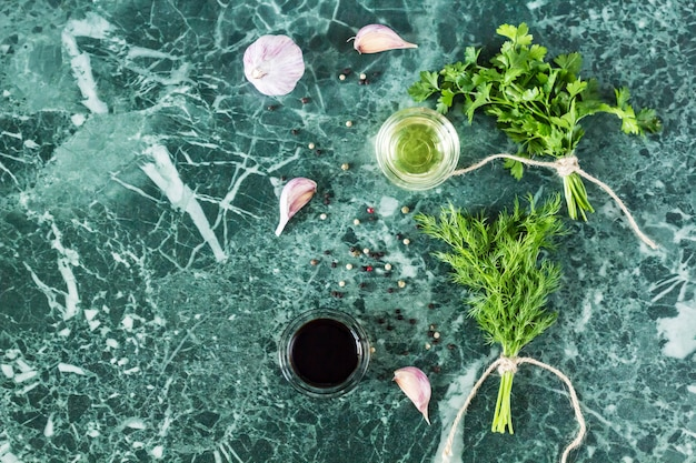 Herbs and spices on marble stone table. parsley, dill, garlic, olive oil, soy sauce and pepper