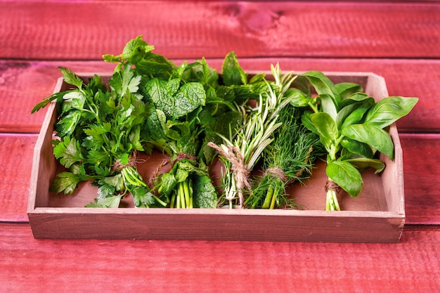 Herbs in a wooden tray on a red rustic table