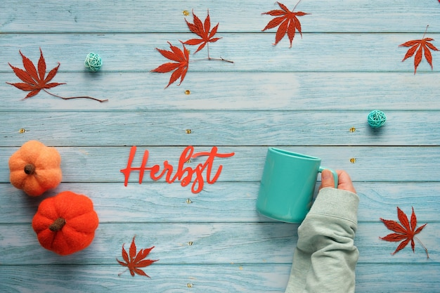 Herbst means autumn in german. seasonal fall flat lay with maple leaves and wool felt decorative pumpkins on lignt turquoise wood. hand holds ceramic mug with word herbst cut out of paper.