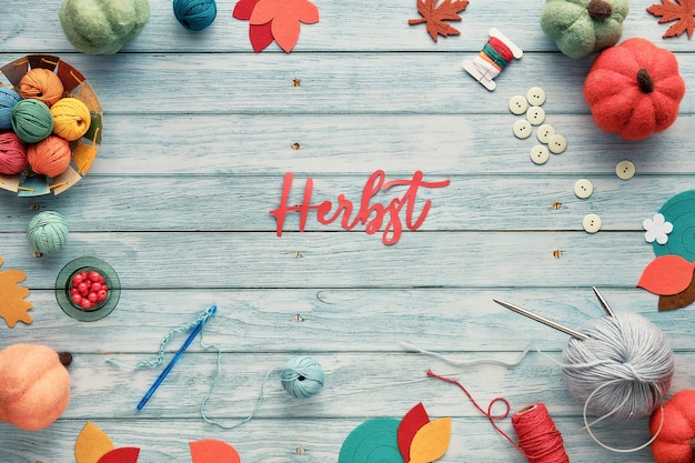 Herbst means autumn in german. text cut out of paper. wool bundles, yarn balls, maple leaves on aged light blue wood.