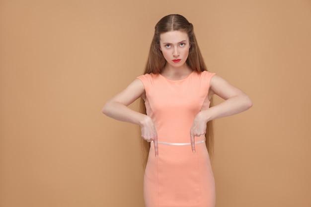 Здесь и сейчас. серьезный босс смотрит в камеру и указывает. портрет эмоциональной милой, красивой женщины с макияжем и длинными волосами в розовом платье, студийный снимок, изолированный на светло-коричневом или бежевом фоне