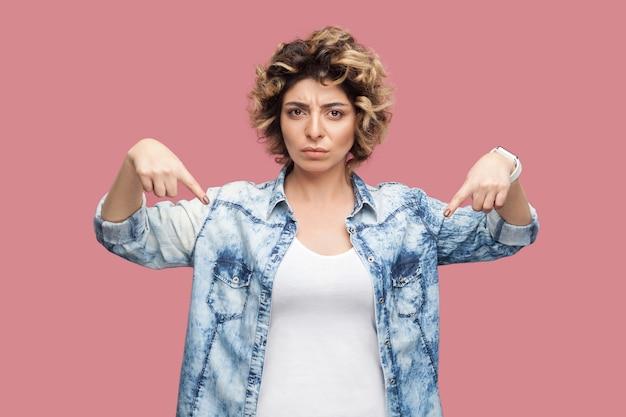 Здесь и прямо сейчас. портрет серьезной властной молодой женщины с вьющейся прической в повседневной голубой рубашке, стоящей и указывающей вниз и смотрящей в камеру. крытая студия выстрел, изолированные на розовом фоне.