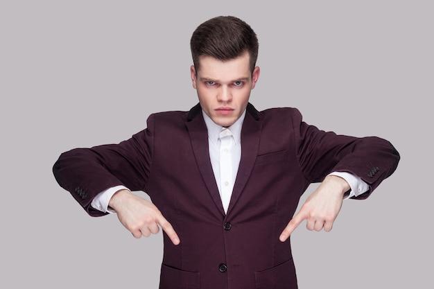 Здесь и прямо сейчас. портрет серьезного красивого молодого человека в фиолетовом костюме, белой рубашке, стоящего, смотрящего в камеру и указывающего вниз с поднятыми руками. крытая студия выстрел, изолированные на сером фоне.